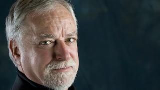 hombre mayor con barba sobre fondo negro