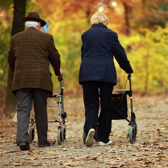 una pareja de personas mayores paseando con andadores