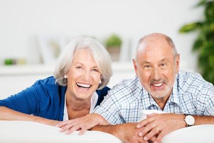 Pareja de mayores riéndose y apoyados en un sillón