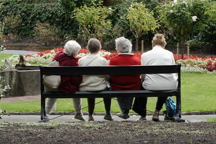 4 mujeres mayores sentadas en un banco