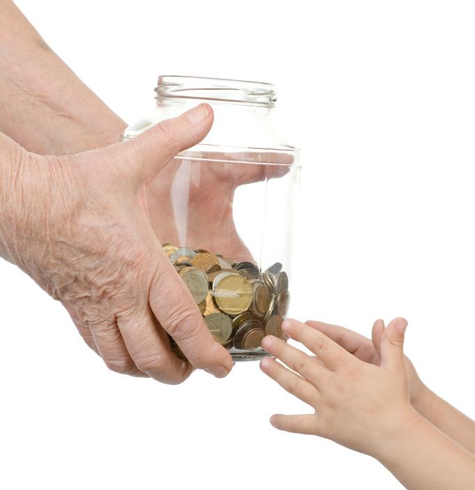 Mano de una abuela dando dinero a su nieto