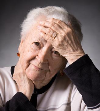 Mujer mayor con mano en la frente