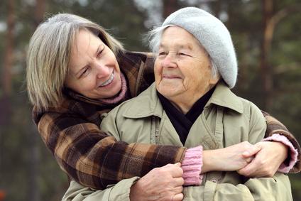 mujer mayor sonriendo y abrazada por su hija