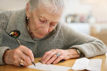 señora mayor escribiendo en la mesa