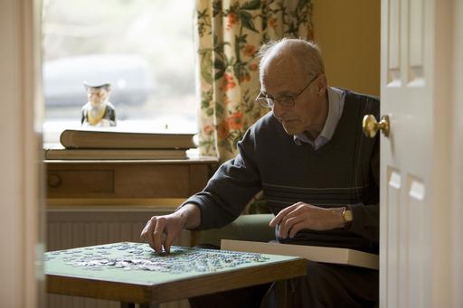 señor mayor escribiendo en su casa